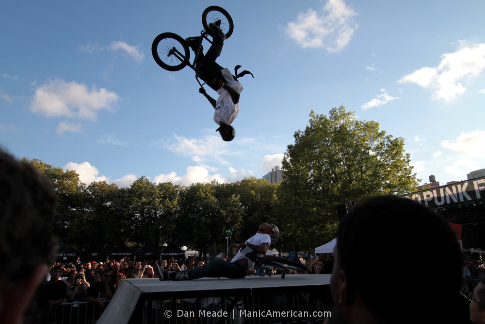One BMXer backflips over another.