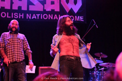 A man opens his shirt on stage at the 2012 NYC Beard and Moustache Competition.