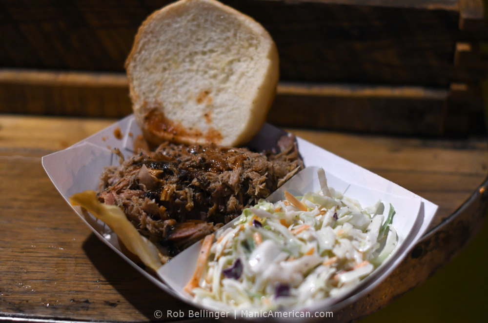 A pork barbecue sandwich with side of cole slaw on a wooden table