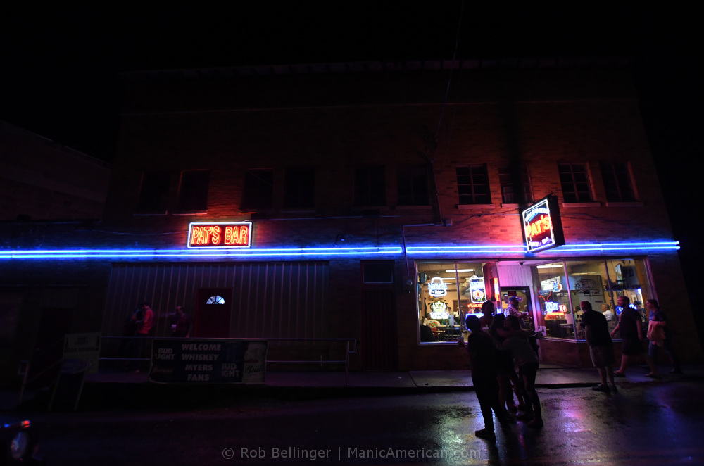 A bar called Pat's with blue neon lights running along the facade. A small corwd is gathered by the entry way at right.