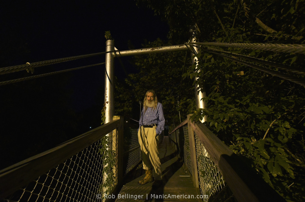 A bearded man standing on a pedestrian swing bridge at night
