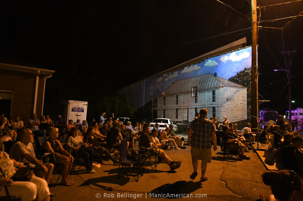 Dozens of people in lawn chairs sitting in front a building with a mural of an old hotel