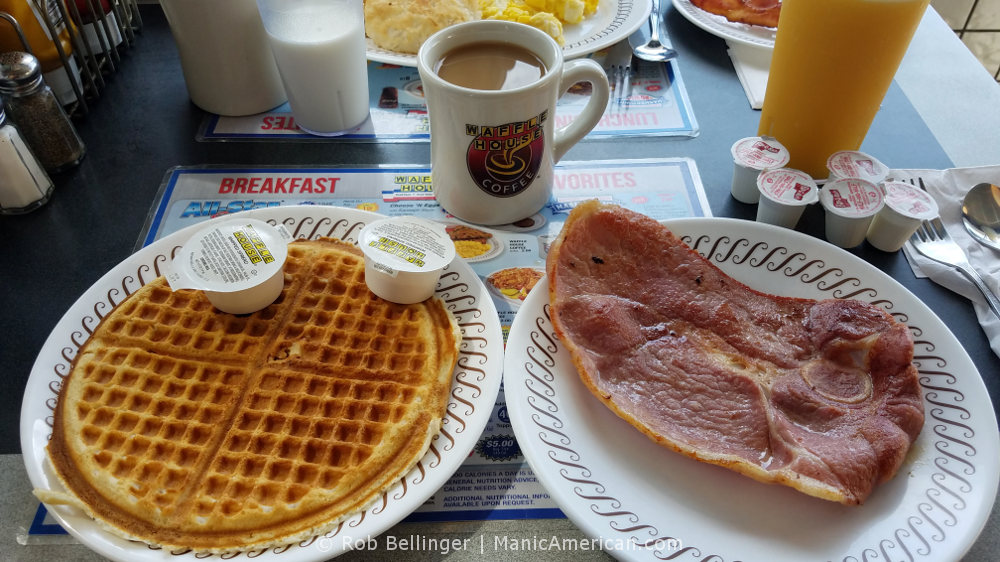 Plates of food at the Waffle House restaurant containing a waffle, a slice of country ham, surrounded by glasses of milk, coffee, and orange juice