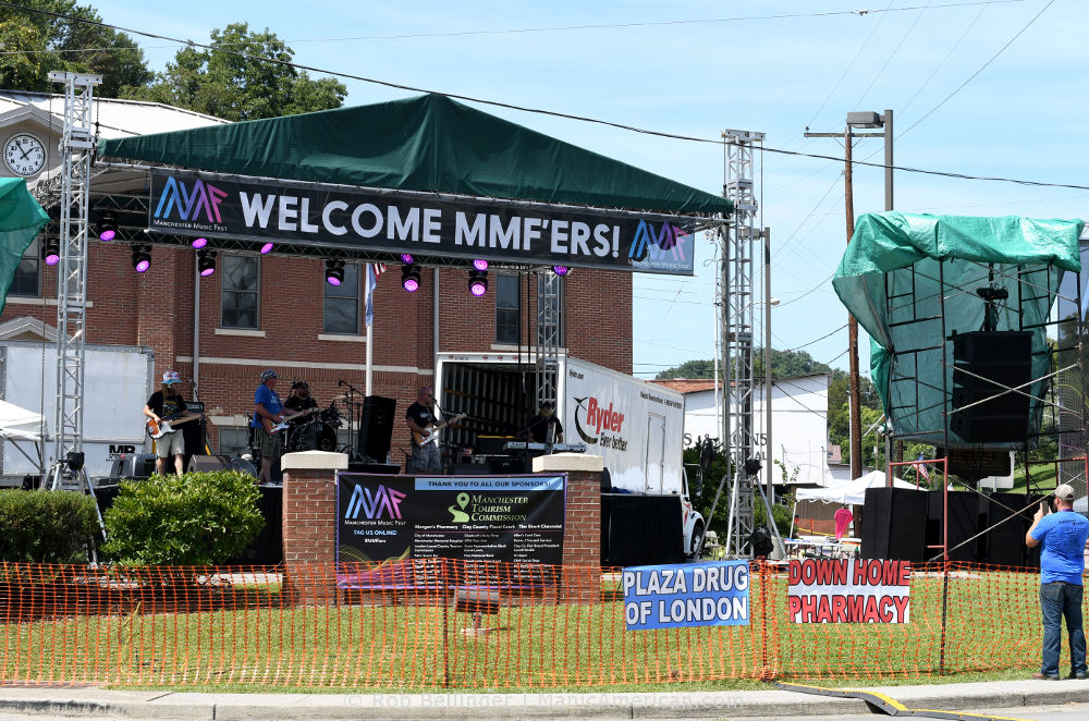 A stage with a large banner that reads WELCOME MMF'ERS in a small town square