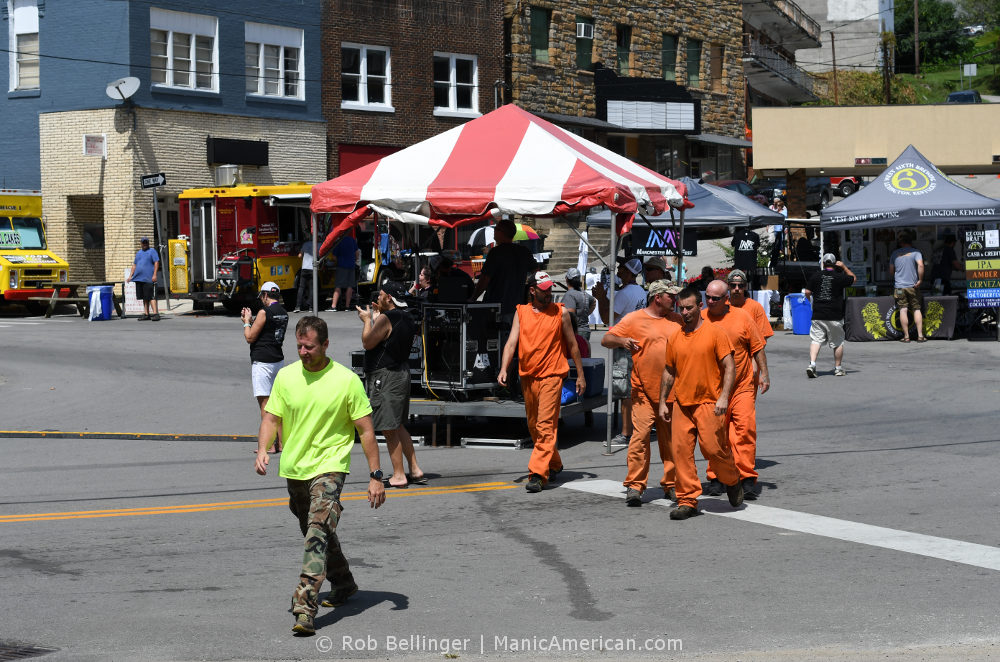 A man leads a chain gang of five prisoners in orange jump suits through a small downtown