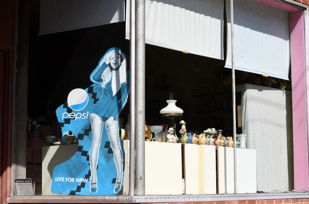 A storefront displaying knick-knacks with a faded cardboard pepsi sign