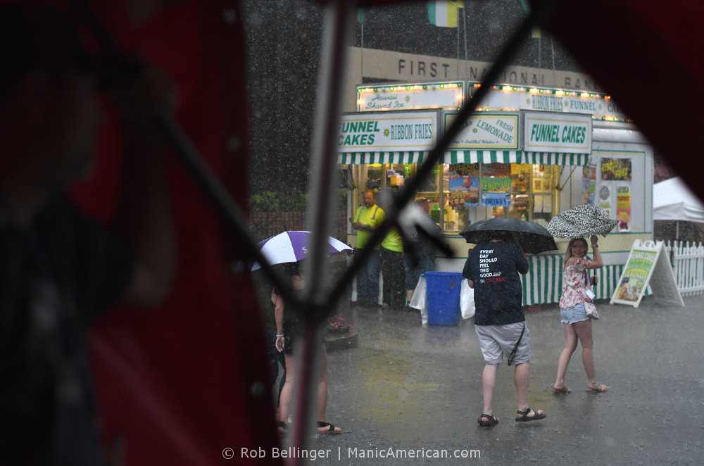 A family walks in pouring rain past a funnel cake stand