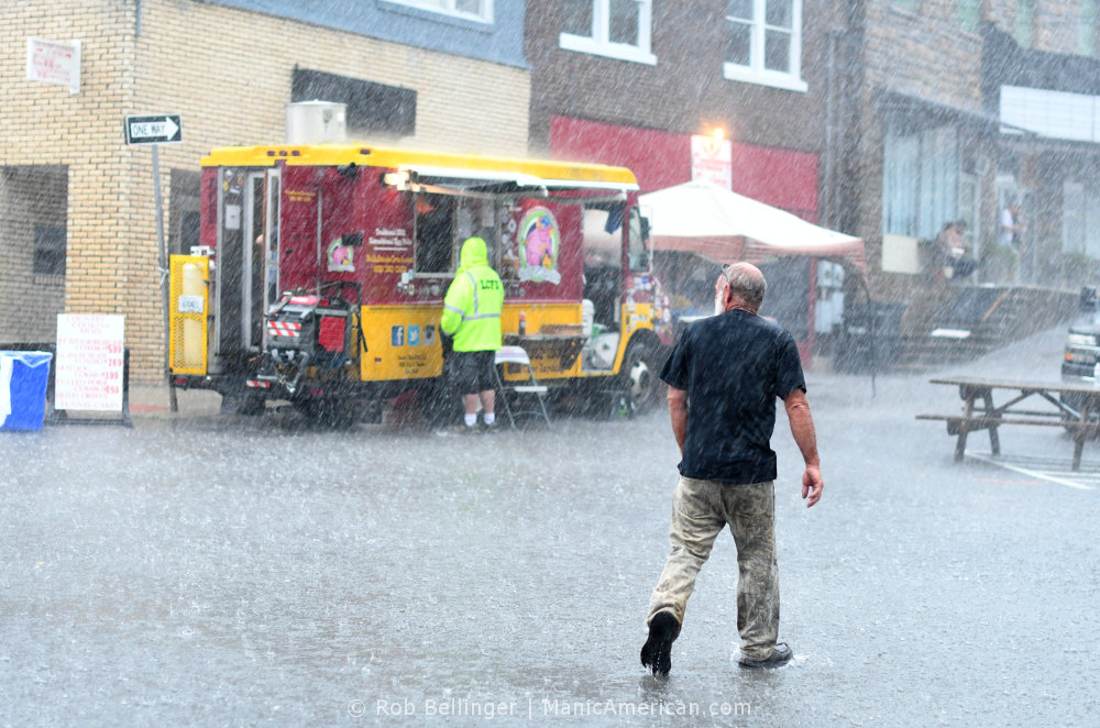 A man walks in pouring rain past a food truck
