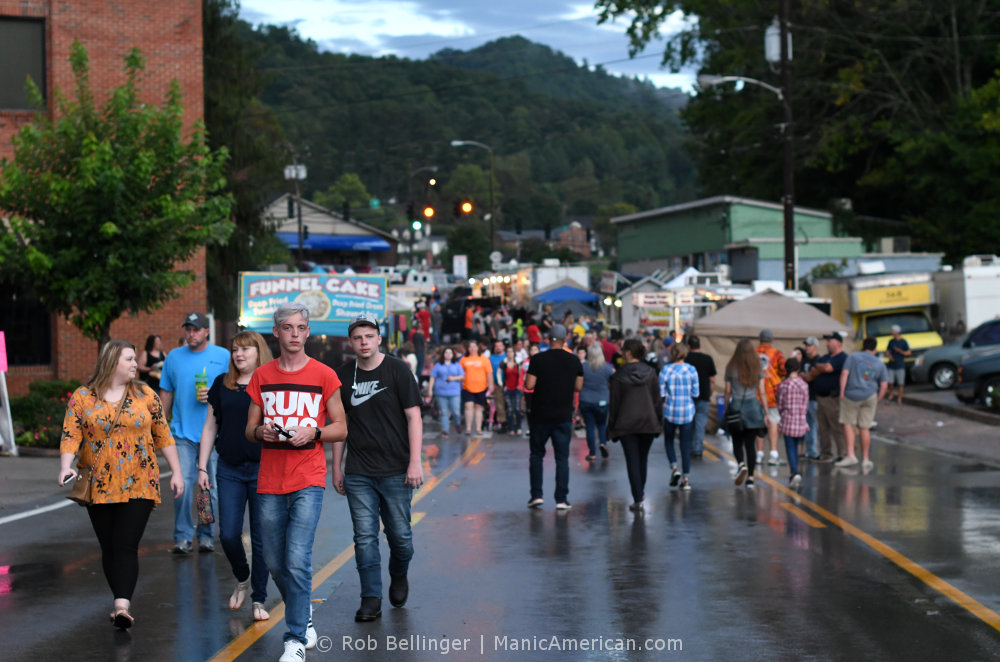 A large crowd of festival goers walking down a wet street with mountains in the background