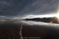 A cloudy sky reflected over the shore of Old Orchard Beach.