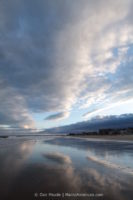 A partly cloudy sky reflected over the shore of Old Orchard Beach.