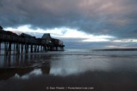 A pier reflected over the shore of Old Orchard Beach.