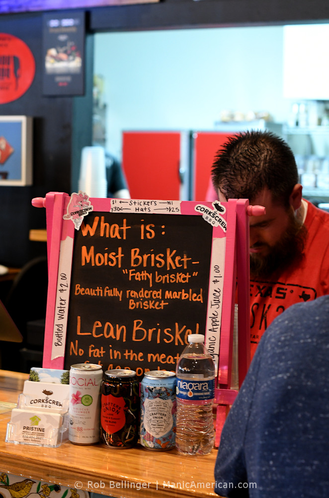 a small blackboard set on the counter of a restaurant with handwritten text explaining the difference between moist and lean brisket