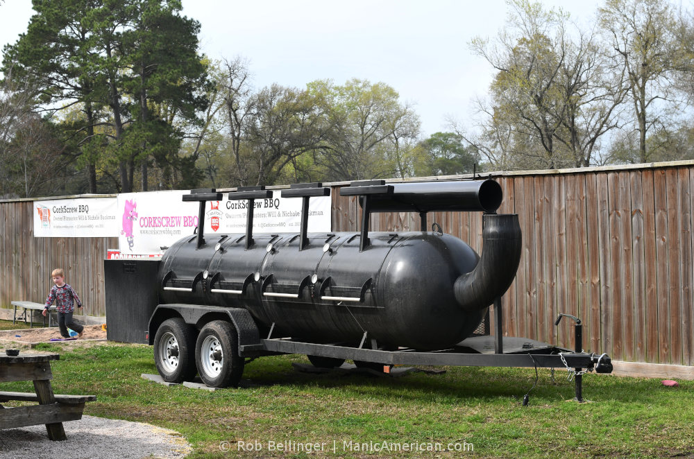 a child plays next to a large steel smoker mounted on a two-axle trailer