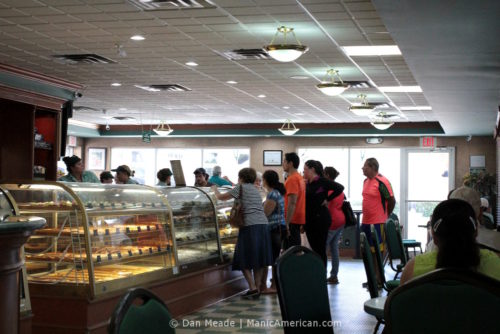 People gathered around Versailles's lunch and pastry counter.