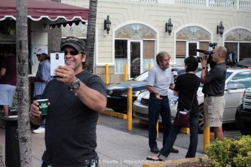 A man takes a photo while a Telemundo news crew interviews a subject.