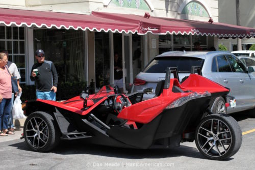 A cherry red Polaris Slingshot parked in Versailles's parking lot.