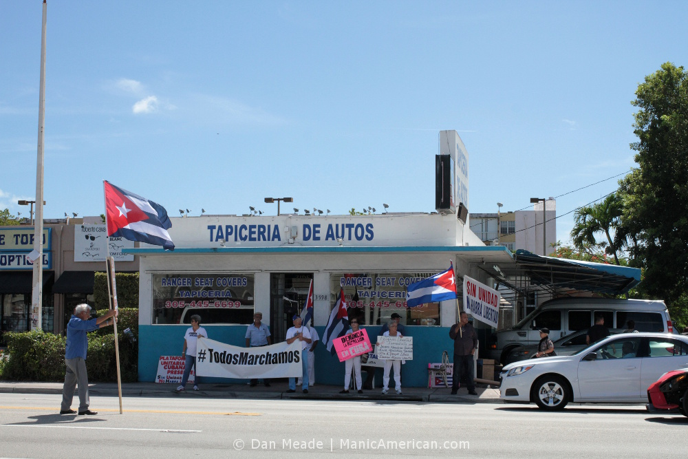 10 #TodosMarchamos 10 #TodosMarchamos demonstrators, across from Versailles in Miami, with signs and flags.