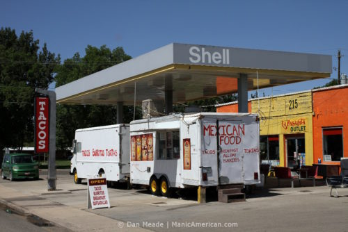 Two food trucks under a former gas station's awning.