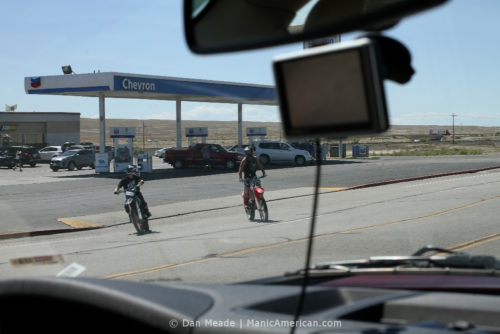 Two motorbikers pull out of a functioning gas station.