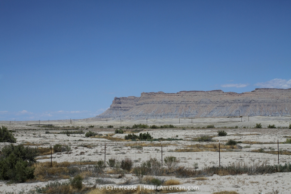 A grey landscape leading to a series of grey buttes.