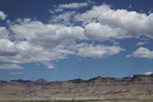 Grey buttes under a series of clouds.
