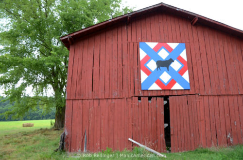 An Amish hex symbol, showing the outline of a cow in front of a geometric pattern, mounted on a red barn on an overcast day