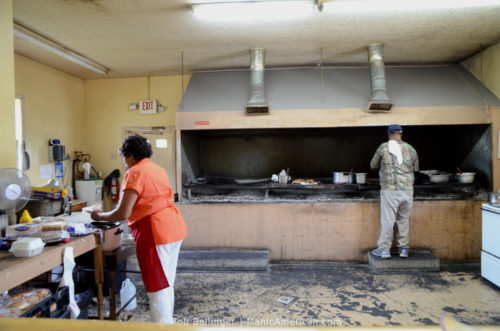 The kitchen of a Kentucky barbecue restarant, with a man tending the grill and a woman scooping beans from a slow cooker.