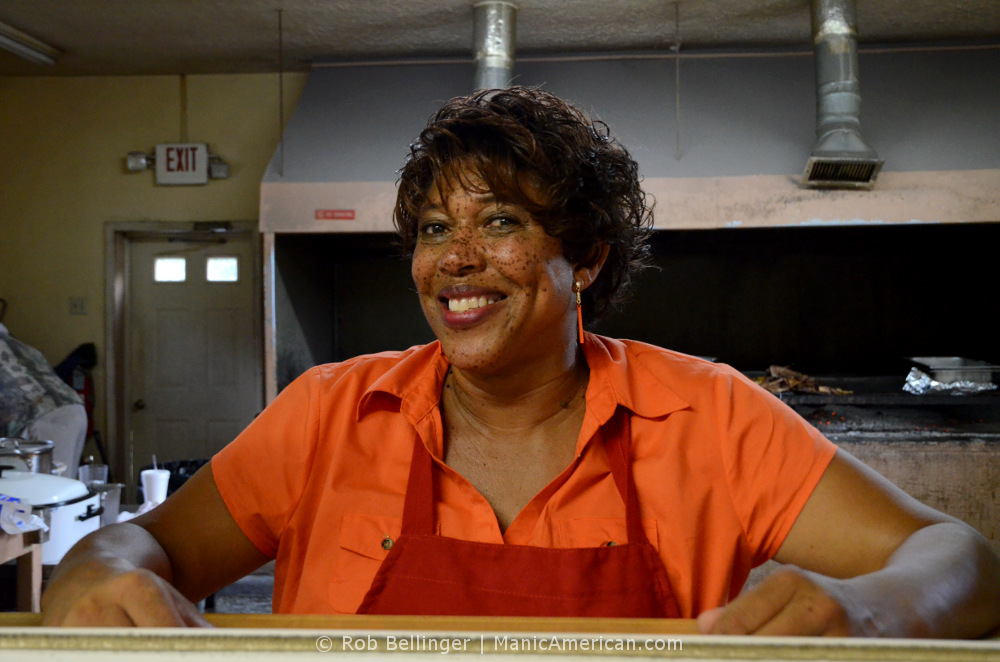 A smiling Black woman wearing an apron, in the kitchen of her restaurant
