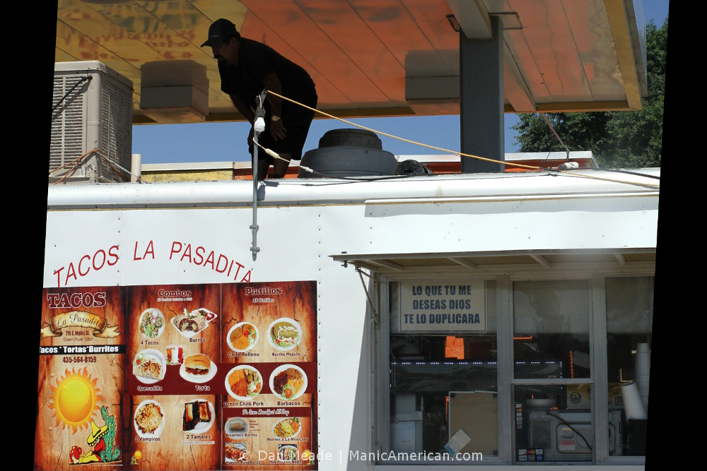 A worker inspects a HVAC unit atop a food truck.