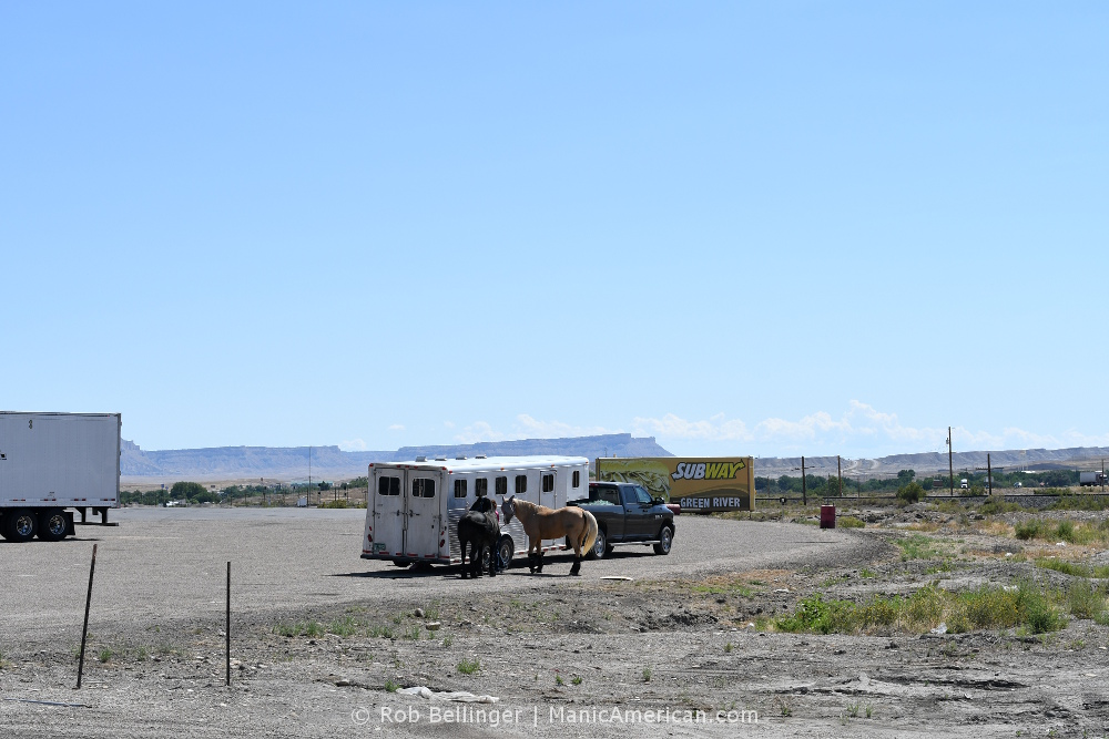 A horse trailer amid a sparse landscape.