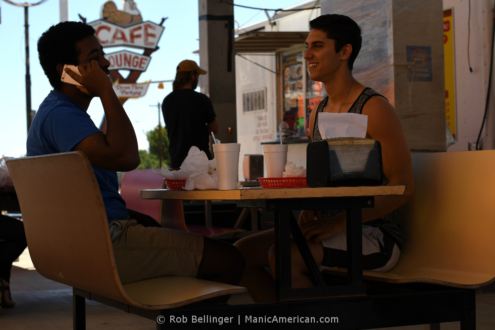 Two people eating outdoors.