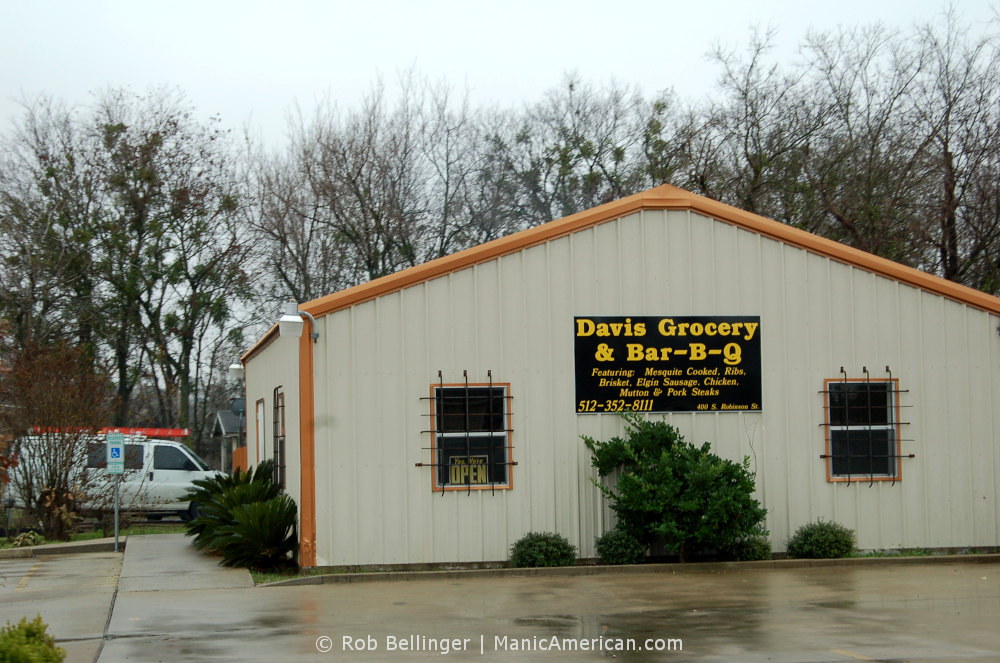 A small building of corrugated steel with a sign that reads Davis Grocery & Bar-B-Q