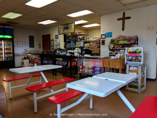 The interior of a small convenience store and restaurant with a wooden cross on the wall, a serving counter, and two metal tables with benches