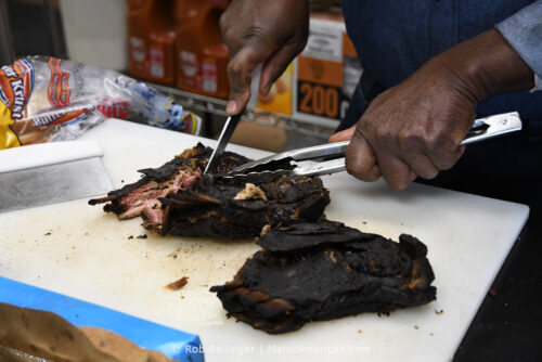 A man's hands use tongs and a knife to break apart two racks of smoked, blackened lamb ribs