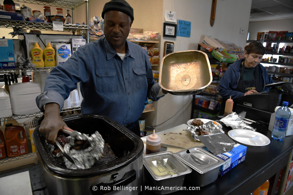 A Black man wearing a denim, button down shirt and winter cap retrieves meats from a slow-cooker at the counter of his restaurant while a woman tallies up an order on the cash register