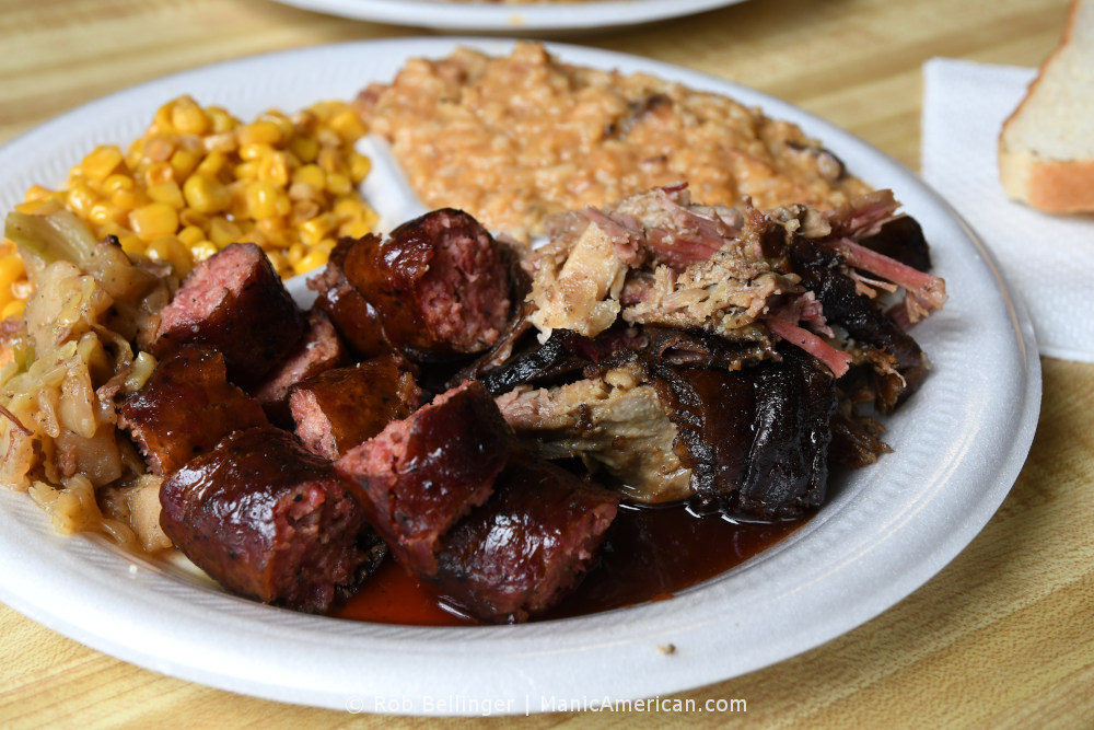 A styrofoam plate containing chunks of sliced sausage, smoked lamb, creamy jambalaya, corn, and boiled cabbage