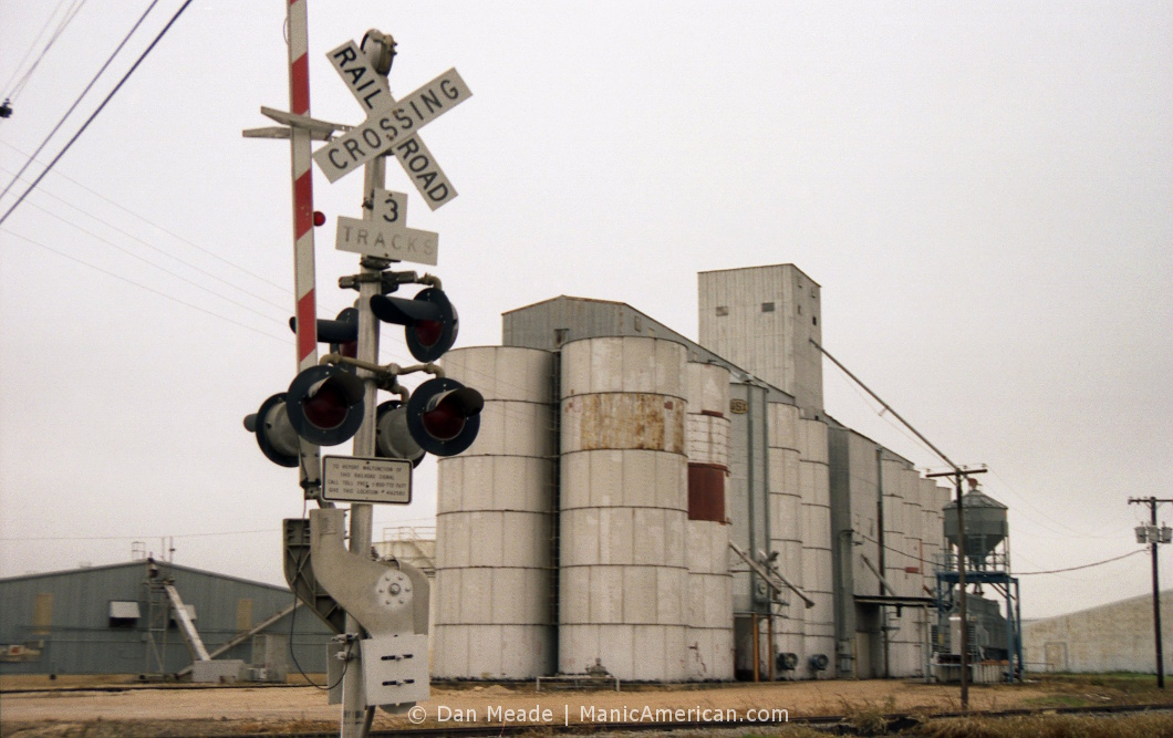 The Williamson County Grain silos beside a railroad crossing.