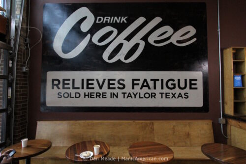 """A sign declares, """"DRINK COFFEE - RELIEVES FATIGUE"""""""