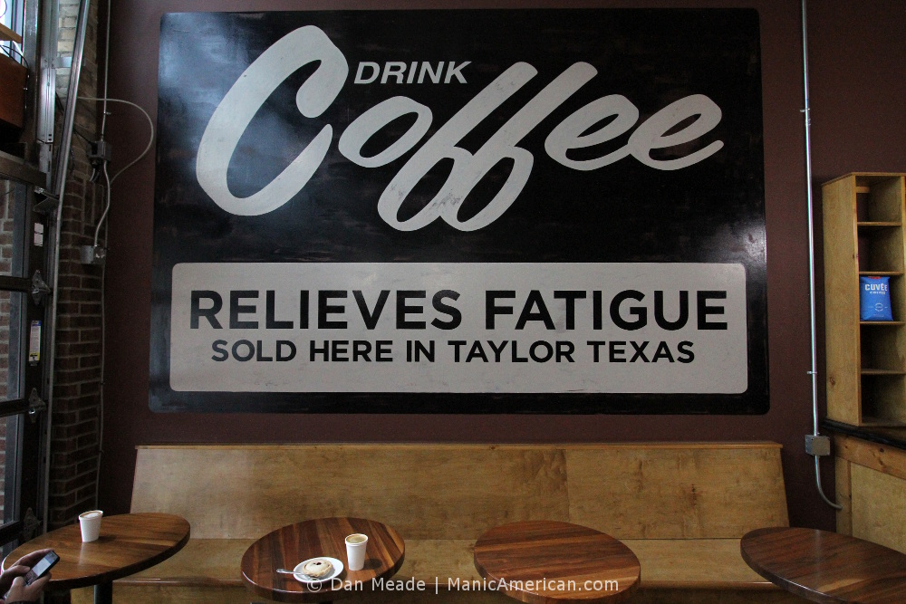 "A sign declares, ""DRINK COFFEE - RELIEVES FATIGUE"""