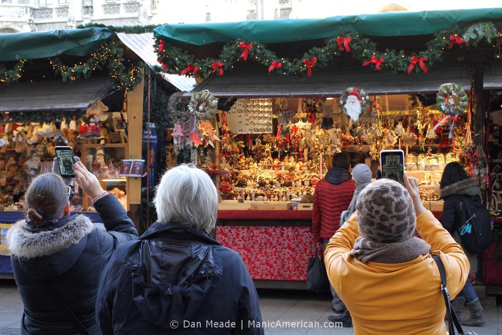 Tourists take photos of Munich's Glockenspiel.