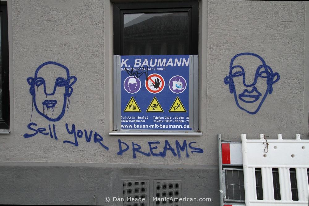 "Graffiti reading, ""SELL YOUR DREAMS."""