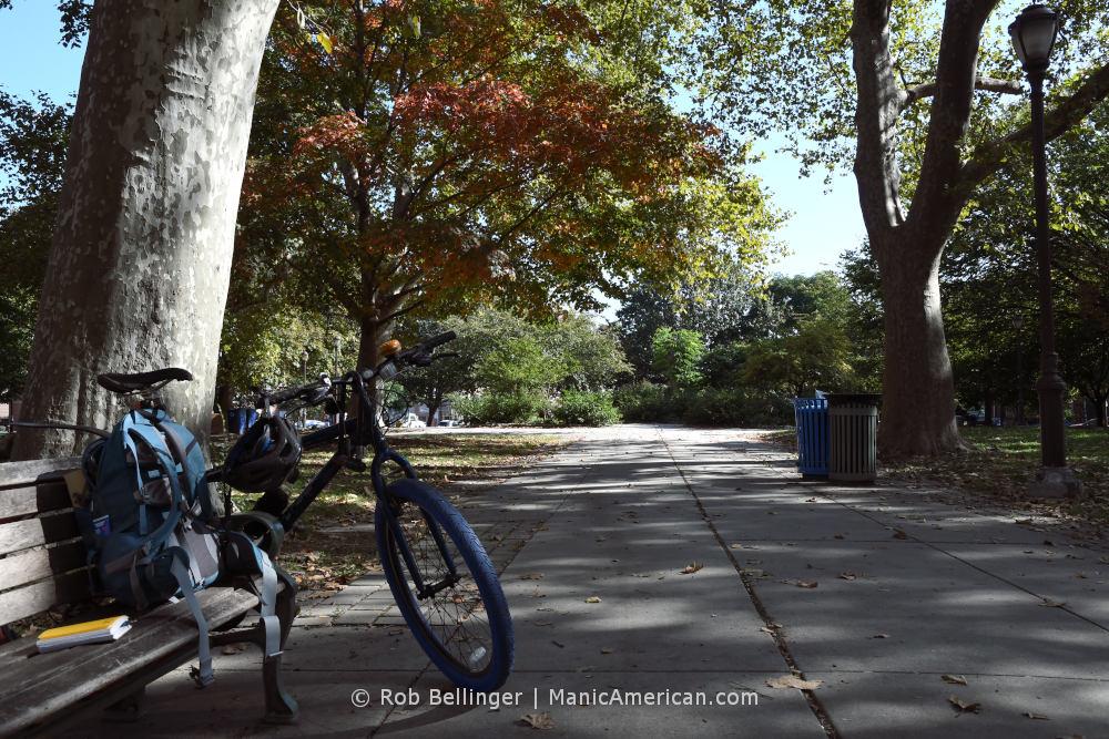 A bike sits against a park bench