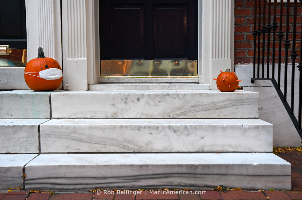 Two halloween pumpkins on a marble stoop, one wearing a mask and one with spikes