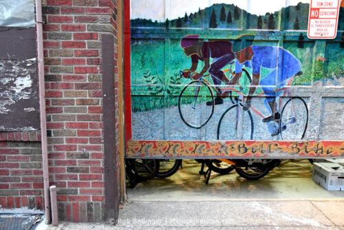 a raised garage door bears a painting of two bikers