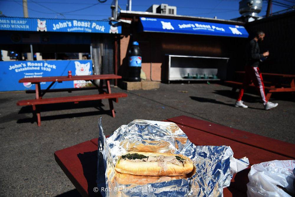 a roast pork hoagie shown in bright sun while a man in red sweatpants walks by