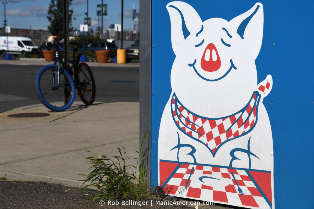 a logo of a pig wearing a bib with a bike in the background