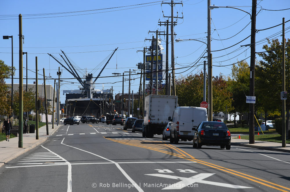A ship unloads cargo at the end of a busy street