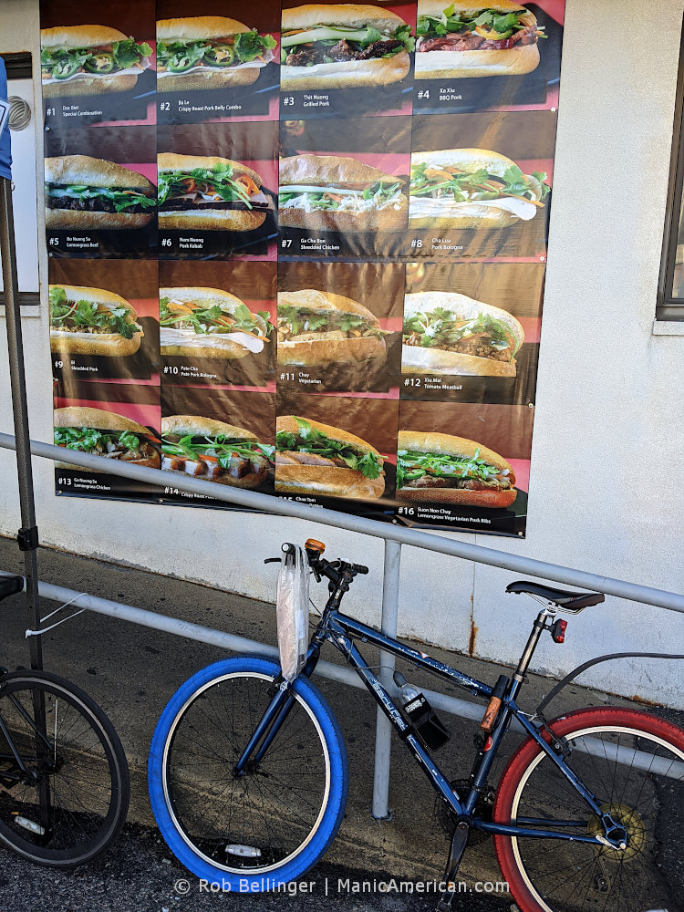 a bike parked outside a building with a vinyl sign advertising 16 different banh mi sandwiches
