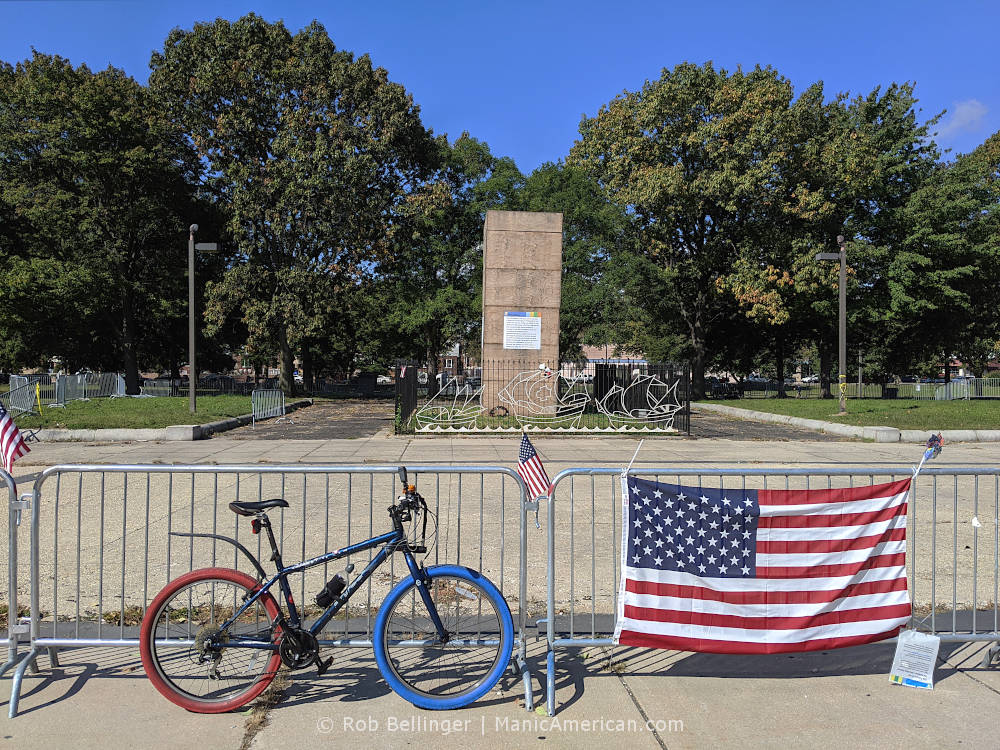 a bike with red and blue tires parked next to a fence with an american flag. in the background, a statue is in a wooden box.